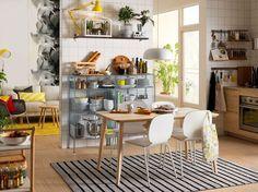 Hvid, sort og gul 1-værelses lejlighed med træbord og hvide stole.