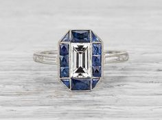 Antique Art Deco engagement ring made in platinum and centered with an approximately .90 carat EGL certified emerald cut diamond with H-I color and SI1 clarity. Accented with sapphires and baguette cu