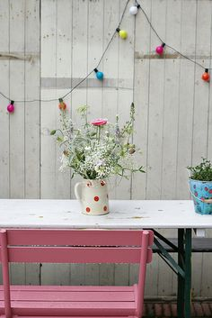 Paint one chair pink and leave the rest in neutrals - add colourful lights and flowers to make the chair blend in.