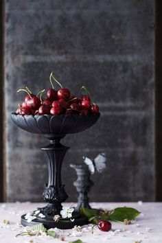Fresh deep-red fruit in an lovely raised serving bowl, with blossoms and butterflies that apparently float in and out of the room at a whim... looks like a scene out of some ancient Greek myth, doesn't it?