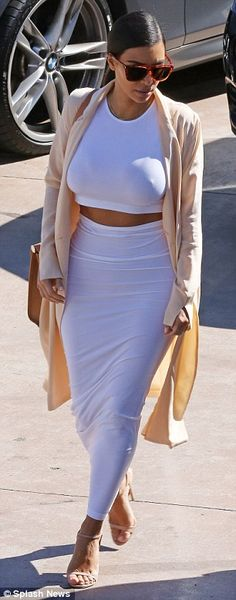 Kim Kardashian shows off her toned midriff in tight white dress #dailymail