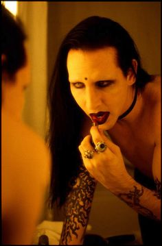 Marilyn Manson putting on lipstick in mirror. I have an enormous amount of respect for this man. Say what u want about him but he's my hero