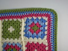 This is a simple Granny Square design which uses four colours, combined in different ways and set against a cream background, to create a bright and sunny blanket.