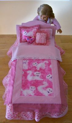 How to make an American Girl doll bed and bedding. The doll bed is a stretched artist canvas that is glued to paper mache letter Es for legs and stapled to a padded, fabric-covered piece of art board.