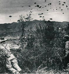 This is the battle of Dien Bien Phu. During this combat, the French fought the Vietminh in a battle in North Vietnam. The rebels defeated the French after 56 days because of sheer numbers and artillery. I would infer the objects being dropped on the parachutes are bombs or soldiers. I would ask what the parachutes are carrying and who was dropping them?