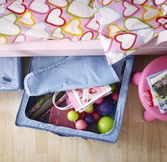 Pohled z ptačí perspektivy na úložný prostor pod postelí IKEA, v němž jsou hračky a kreativní materiály.