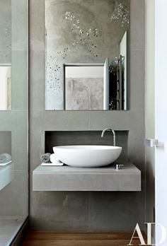 Glass mosaics, seen in the mirror, decorate the master bath in this contemporary London residence designed by Monica Mauti   archdigest.com