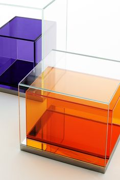 BOXINBOX design #PhilippeStarck #glasitalia #Salone2015 | Low tables and storage furniture, designed like a box within a box, in thermo-welded extralight glass. These are placed on a base of reflective polished stainless steel. Internal element in transparent coloured glass (in the finishes: viola 98, arancio 101, verde 103, light grey, dark grey and sun yellow). Low display case table low storage table with six shelves in the same above-described finishes.