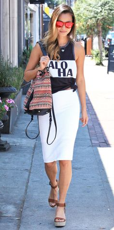 """Jamie Chung made quite a statement while out in West Hollywood. She elevated her knotted """"Aloha"""" graphic tank with a white pencil skirt and neutral espadrilles. A printed Elizabeth & James sling bag and red mirrored shades added playful touches. #InStyle"""
