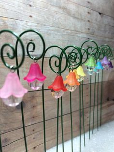 Hanging Lantern Flower with Shepherds Hook. www.teeliesfairygarden.com . . . Welcome the New Year with a bright and well-lighted fairy nook! These lanterns may not light up but the fairies will surely work their magic. You can also get adorable fairy lights here. #fairyscoop
