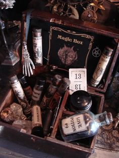 Wooden box from the 1800's holds little vials of wormwood, mandrake, mugwort, frankincense and myrrh granules, stinging nettle, blood of bat and snake oil (novelties), a real animal claw foot, real hair of black cat, a black candle, matches, lucky mini 13 card, Hand of Glory and inverted pentagram talismans, chunk of iron pyrite, crystal rock, antique Italian scooping spoon and a very old bottle with love potion. Wicked Wares by Crystal. Gothic Rose Antiques.