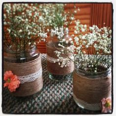 Cheap DIY centerpieces. Save all glass jars used from pickles, tomato sauce, etc. wrap twine around jar and add lace and flowers!