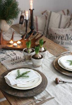 dessous d'assiettes en bois et des branchettes de sapin sur la table de Noël