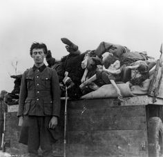 Bergen Belsen, Germany, An SS soldier standing next to a truck loaded with corpses, after the liberation, April 1945.