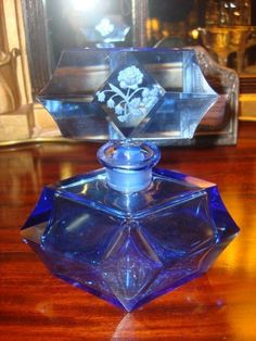 Art Deco period cobalt blue cut glass scent bottle with etched flowers to stopper centre. Maker is unknown.  Gorgeous large scent bottle with many cut and bevelled angles, and large matching stopper, for an overall striking effect.  1930-1940