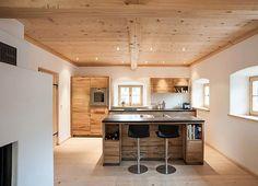 Eine offene Küche im Altholzstil. Die Kücheninsel mit angehängter Theke dominiert. Im Hintergrund die Silhouette der Hochschränke und weiterer Arbeitsf