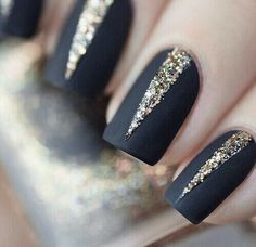 Matte black nails with gold glitter.