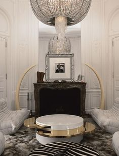Lenny Kravitz Paris apt living room white glam fur chandelier 1970s brass table fireplace tusks