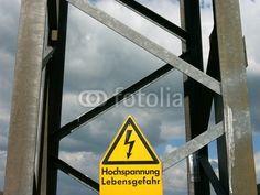 Gelbes Warnschild an einem Strommast im Salzbödetal in Salzböden bei Lollar in Hessen