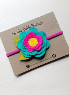 This two tone felt rose layered headband is made with 100% wool felt. The headband includes an extra large layered wool felt rose with a yellow center and bright green leaves. The flowers are attached to a stretchy nylon headband. Nylon Headbands are one size fits most and are