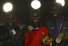 Uganda's gold medalist Stephen Kiprotich (C), Kenya's silver medalist Abel Kirui (L) and Kenya's bronze medalist Wilson Kipsang Kiprotich pose on the podium of the men's marathon during the closing ceremony of the 2012 London Olympic Games at the Olympic stadium in London on August 12, 2012.