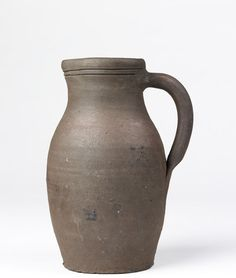 Jug of dark red earthenware. Ovoid body, slightly spreading mouth with projecting lip, loop handle. Round the top are two incised lines. Staffordshire(probably, made) 16th century (made) Height: 9 1/8 in , Diameter: 5 1/4 in. Found early 19th C in excavations at Stoke on Trent. Originally thought to have been 15th or 16th C. A nearly cylindrical pot of similar ?, found at High Str, Cheadle on Nov 14 1934 containing 900 coins of the reign of Edward VI and Elizabeth.
