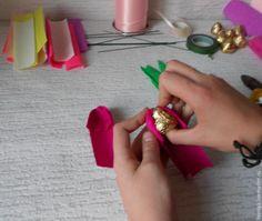 Подготовим материалы и инструменты: - гофрированная бумага; - флористическая проволока; - скотч; - тейп-лента; - декоративная лента; - упаковочная бумага; - кусачки; - ножницы; - конфеты. Режем проволоку пополам. Нарезаем гофрированную бумагу полосками шириной 4-4,5 см. Семь разноцветных полосок для тюльпанов готовы. Зеленую бумагу нарезаем для листочков шириной 2 см.