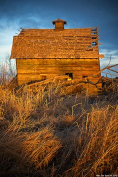 """""""Sunlight And Decay""""  An old abandoned leaning barn reflects the sunlight of golden hour against the skies of Colorado on the eastern plains."""