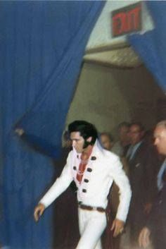 Elvis entering auditorium surrounded by security