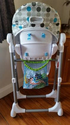 Attach a bath toy storage bag on the back of highchair for bibs and highchair tray toys! This one is from Kmart and I just removed the suction bits.