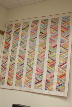 A great way to use scraps. Thin strips sewn together and then cut with a 60 degree ruler.