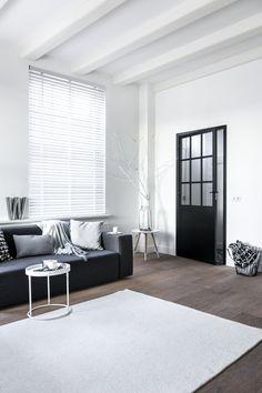 In de woonkamer houd je de ruimte licht en ruimtelijk met witte houten jaloezieen!