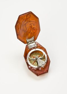 An amber octagonal box, containing a silver compass, the lid carved with a dove, North German, circa 1690.