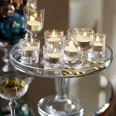 A glass cake plate with clear votive holders and tea lights.