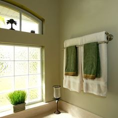Hang a double towel bar above your bathtub -- useful and decorative, all in one.