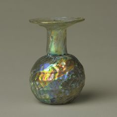 This Roman glass bottle was originally clear. Over the years, water and atmospheric pollution have created many thin layers of glass on the outside of this object, which has given it an attractive metallic sheen or iridescence. Accession number 1977.113.43