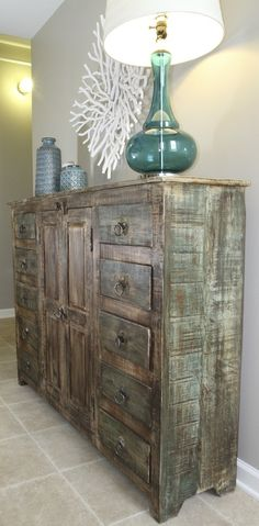 turquoise glass lamp distressed wood sideboard