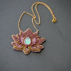 Bead embroidery necklace/pendant of lotus flower. Theres a beautiful turquoise cabochon in the centre. It is backed with natural leather and comes on a metal necklace in gold. The necklace is 41cm long, the beaded part is 7x8 cm. For other beaded necklaces and pendants please see: https://www.etsy.com/uk/shop/Rudasbeading?ref=seller-platform-mcnav&section_id=15132022