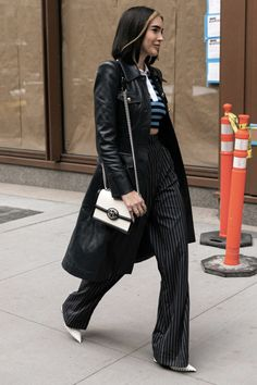 black leather trench coat, blue striped top, black pinstripe pants, white purse and heels Nyfw Street Style, Cool Street Fashion, Street Style Looks, Long Leather Coat, Leather Trench Coat, Black Leather, Trench Coat Outfit, Trench Coats, Blazer Off White