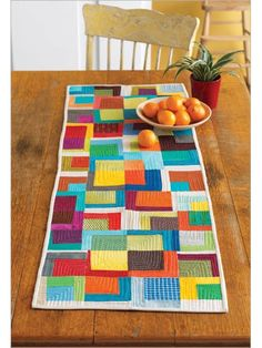 Improvisational cutting and piecing give this patchwork table  runner and placemat fresh design. With key elements of the blocks aligned, the  pattern still comes through so you can enjoy quilting your own inspired mix of  colorful fabrics.