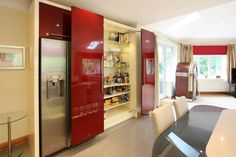 A completely contemporary design with a retro twist, finished with granite worktops and plinth lighting. The large space allowed us to use strong colours and a mix of striking linear furniture alongside curves. This kitchen was specially designed to accomadate a wheelchair, and so we have incorporated wider spaces between units for easy acess and a lowered work top for easy reach.Designed and Fitted by Earle and Ginger Kitchens.
