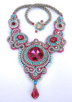 This necklace was my entry for the Fashion Colorworks 2012 competition where it won the Best Use of Color award.The necklace features a large Fuchsia Swarovski cabochon with adjesent Fuchsia Swarovski rivoli, wrapped in soutache in Fuchsia, Turquoise and solver and embellished with silver crystals, ABx2 Turquoise Swarovski crystals and seed beads. The strap is made of gun metal seed beads and finished with a beaded clasp. Measures about 20 inch.