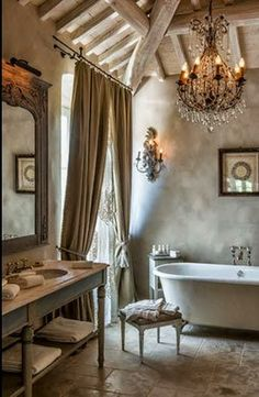 Love so many things about this French bathroom. The tub, the beams, the open vanity, a sparkling chandelier, and the plush draperies.