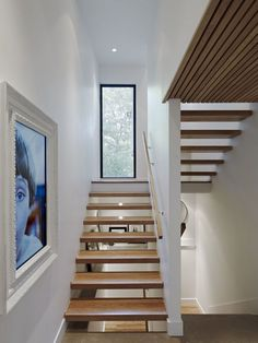 This modern set of wood stairs with a wood hand railing lead to the upper floor of the home. A large white framed digital picture decorates the wall, while a vertical window provides glimpses of the trees outside.