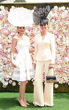 One woman stunned in an all-white ensemble while her companion was a vision in a cream tro...