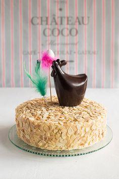 Mona de Pascua: tarta de bizcocho relleno de chocolate, con crema de mantequilla y almendras, rematada por una figura de chocolate. Receta paso a paso.