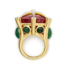 Pink tourmaline, emerald and diamond ring by Tony Duquette; side view.  Centering a shield-shaped pink tourmaline surmounted by round brilliant-cut diamond starburst detail within an openwork mount accentuated by oval cabochon emeralds;