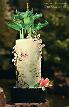 Hand-painted wedding cake with green Chinese pagoda, pink lotus flower and cherry blossoms.