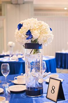Event centerpiece. Cylindrical vases, water, roses, hydrangeas, gold wire.