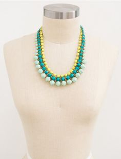 Fiji If you can't head to the tropics, then wear them around your neck! You're sure to feel the warmth of the sand and cool of the waves with this combination of teal, aqua, and lime. Pairs perfectly with a summer dress and an ice cold lemonade. Fastens with a button clasp.